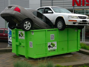 cars piled high in a dumpster