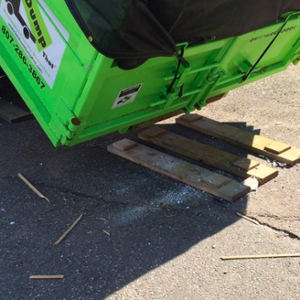 Dumpster Being Dropped on Boards