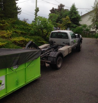 Roll Off Dumpster Getting Lifted Onto Truck